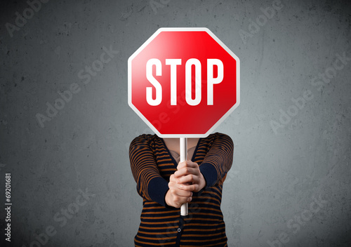 Obraz Young woman holding a stop sign - fototapety do salonu
