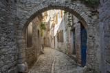 Fototapeta Uliczki - Old and narrow street, paved of cobble stones, Bale, Croatia