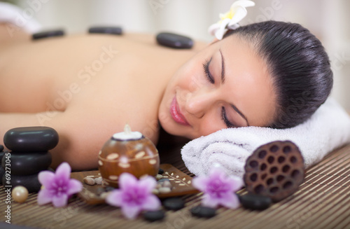 Obraz na plátně  beautiful woman in spa salon with hot stones in back