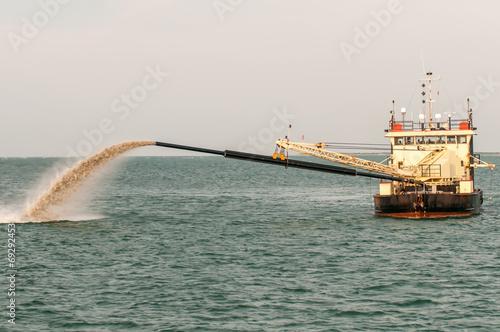 Valokuva  Barge Pipe pushing sand onto the beach