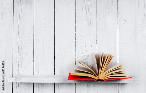 Fototapety, obrazy: The open book on a wooden shelf.