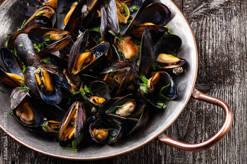 Staande foto Schaaldieren Boiled mussels in copper cooking dish on dark wooden background