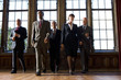 Small group of businessmen and woman walking in hall, low angle view