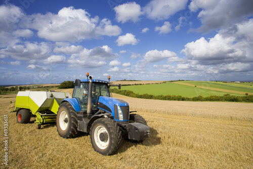 Tractor and baler baling straw in sunny rural field Canvas Print