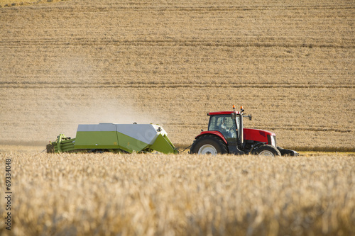Photo Tractor and straw baler in sunny, rural field