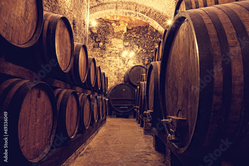 Fotografering Wooden barrels with wine in a wine vault, Italy