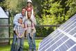 Happy family standing near large solar panels