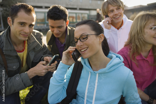 Fototapety, obrazy: A young woman talking on a mobile phone with her friend smiling
