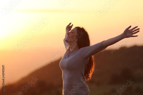 Foto  Woman at sunset breathing fresh air raising arms
