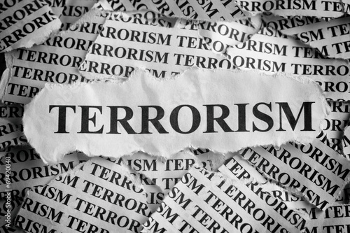 """Fotografía  Torn pieces of paper with the word """"Terrorism"""""""