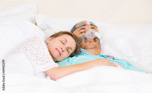 Man with sleeping apnea and CPAP machine asleep in bed Canvas Print