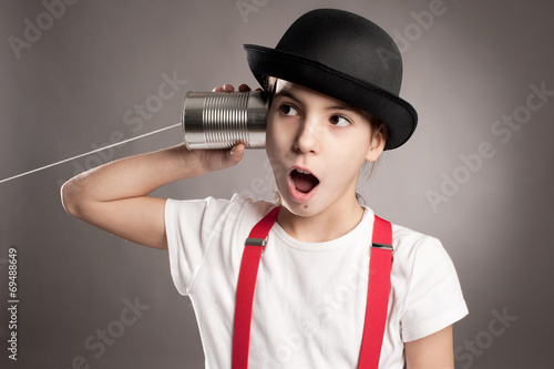 Photo  little girl using a can as telephone on a gray background
