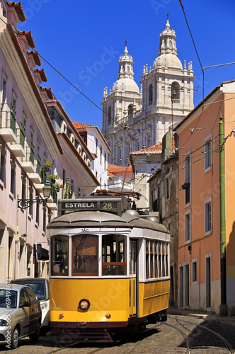 Fotografia  Narrow street in old Lisbon downtown with typical yellow tram