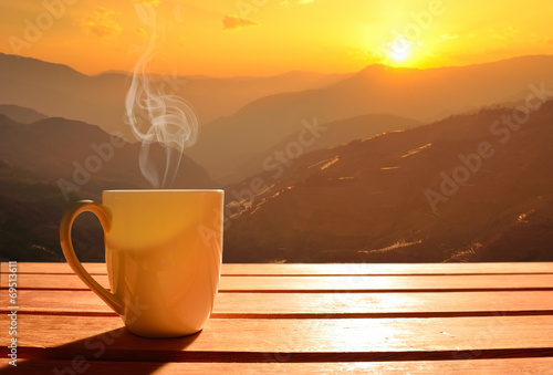 Tablou Canvas Morning cup of coffee with mountain background at sunrise