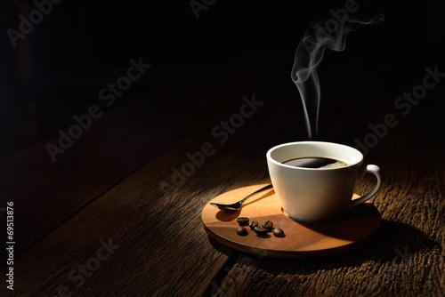 filizanka-kawy-z-dymnymi-i-kawowymi-fasolami-na-drewnianym-tle