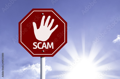 Photo  Stop Scam red sign with sun background