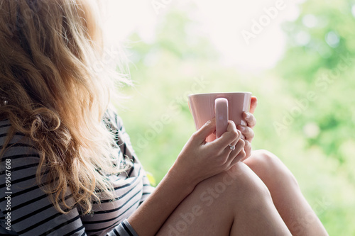 Deurstickers Ontspanning Peaceful woman relaxing at home with cup of tea or coffee
