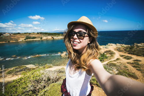 Foto  Pretty young female tourist takes travel selfie at the beach