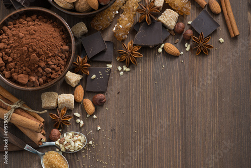 Poster Chocolade chocolate, cocoa, nuts and spices on wooden background, top view
