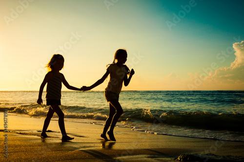 Fototapeta happy kids playing on beach at the sunrise time obraz na płótnie