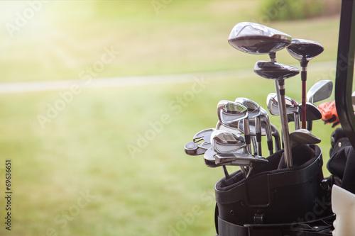 Deurstickers Golf set of golf clubs over green field background