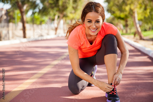 Happy runner tying her shoes