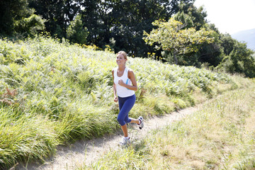Fototapeta Do klubu fitness / siłowni Athletic woman running in countryside