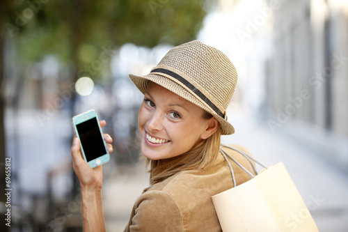 Foto  Smiling shopping girl using smartphone in town