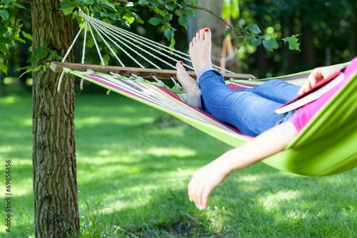 Valokuvatapetti Lady lying with book on hammock