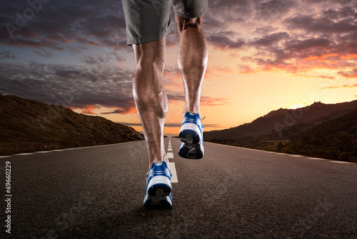 Fotografiet  Close up of athlete running on the empty road