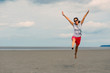Happy woman jumping on the beach in front of Mont Saint Michel a