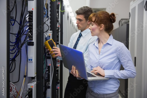Fototapety, obrazy: Team of technicians using digital cable analyser on servers