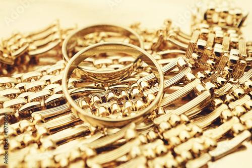fototapeta na szkło Złote pierścionki i naszyjnik na złotym tle
