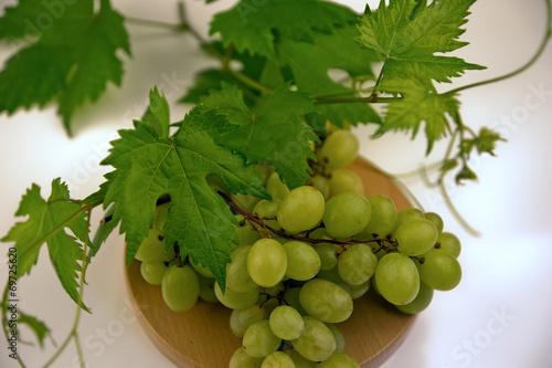 Stampe  Grüne Weintrauben mit Blättern