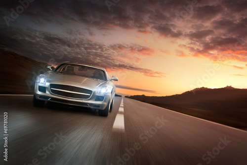 Cuadros en Lienzo Luxury sports car speeding on empty highway at the sunset