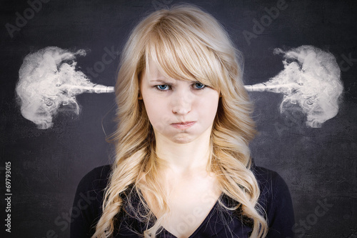 Angry young woman, blowing steam coming out of ears