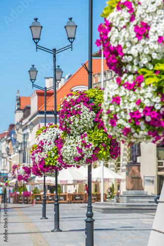 Obraz Kolorowe kwiaty na latarni ulicznej w tle rynku - fototapety do salonu