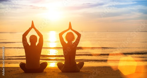 Staande foto School de yoga Yoga silhouette of a young couple on the beach at sunset.