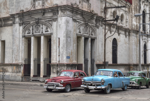 In de dag Havana Cuban taxis passing under an old church in Havana