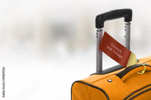 Fotografija  Trinidad and Tobago. Orange suitcase with label at airport.