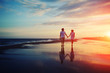canvas print picture - Happy romantic couple walking and holding hands on a beach