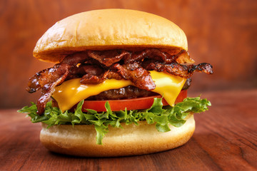 Bacon burger with beef patty on red wooden table