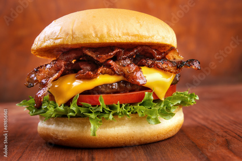 Bacon burger with beef patty on red wooden table Fototapeta