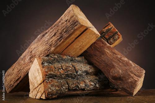 Fotografia, Obraz Heap of firewood on floor on dark background