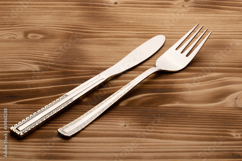 Fotografia, Obraz Knife and fork set on a wooden vintage table