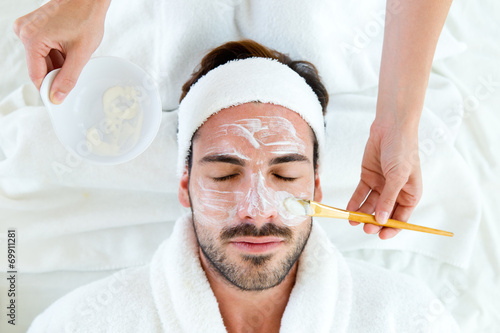 Fotografie, Obraz  Man with clay facial mask in beauty spa.