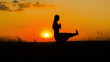 Silhouette of a Young Girl Practicing Yoga At Sunset