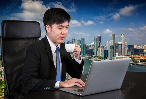 Photo  Portrait of goodlooking Asian man sitting at table at working of