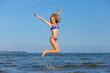 cheerful girl jumping at sea
