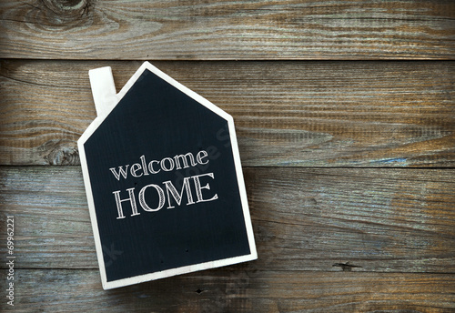 Valokuva  House Shaped Chalkboard sign on rustic wood WELCOME HOME
